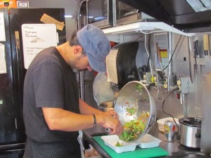 Chef Norman Zeledon, of The Galley prepares his lobster potato cake on a bed of salad and coleslaw.