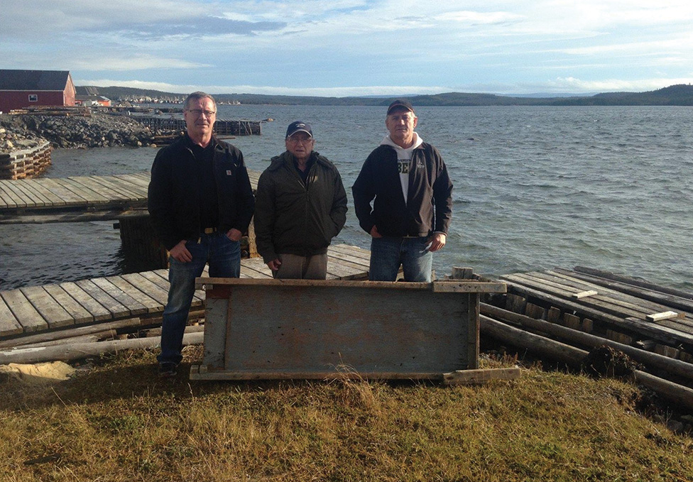 Rene, Raymond and Maurice Ryan with the wooden fish chute that saved the lives of Maurice and his father, Raymond in August, 1991. Photo; courtesy of Maurice Ryan, taken November 22, 2015.